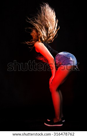 Twerking young woman over black background - stock photo