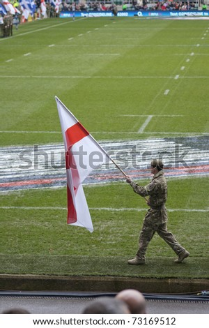TWICKENHAM LONDON - MAR 13: Soldier parades english flag at England vs Scotland, England playing in white Win 22 -16, at RBS Six Nations Rugby Match on March 13, 2011 in Twickenham, England. - stock photo