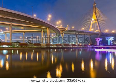 Twilight at Suspension bridge and road interchange river front view - stock photo