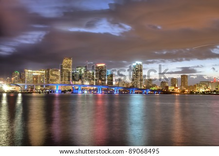 Twilight glow on skyline of Miami along Biscayne Bay on cloudless, calm evening. - stock photo