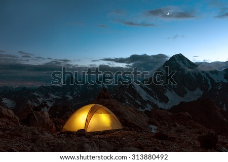 Twilight Mountain Panorama and Tent Illuminated Camping Yellow Tent Night High Altitude Alpine Landscape Crescent in Dark Blue Sky warmer tone - stock photo