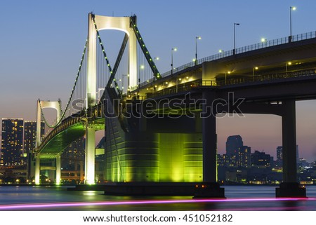 twilight of Tokyo Rainbow bridge and the light trails of boat in Odaiba city, japan