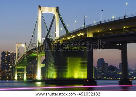 twilight of Tokyo Rainbow bridge and the light trails of boat in Odaiba city, japan - stock photo