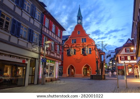 Twilight scene in the small town of Lahr in the Black Forest, Germany (province of Baden Wurttemberg) with focus on the red building of the Town Hall. - stock photo