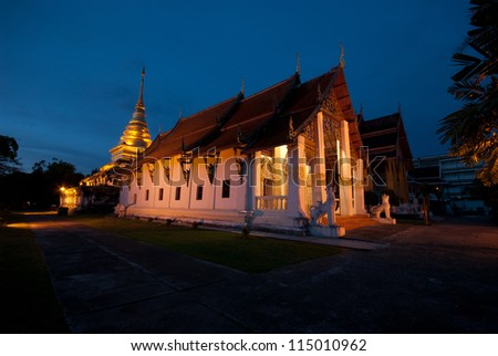 Twilight scene of Ancient pagoda and church in Wat Phra Tras Chang Khum temple,Nan province in Northern of Thailand. - stock photo