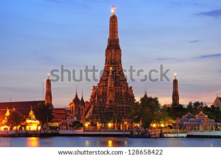 Twilight time of Wat Arun across Chao Phraya River during sunset in Bangkok, Thailand