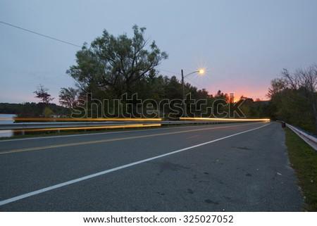 Twilight view of a causeway across Pontoosuc Lake in Pittsfield, Massachusetts. - stock photo