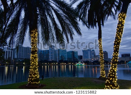 Twilight view of Orlando skyline during the Christmas holidays. Lake Eola and decorated palm trees in foreground. - stock photo