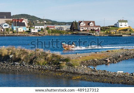 Twillingate, Newfoundland - Sept 13, 2016: Fisherman is driving his motor boat from an early morning fishing trip in the open sea into the town