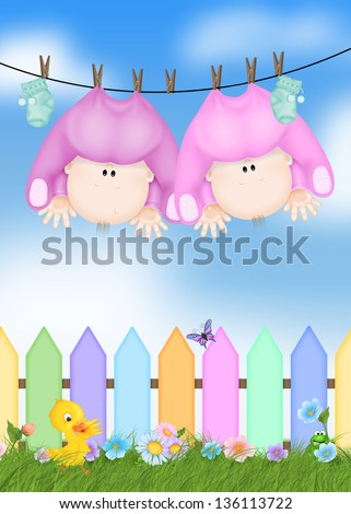 twin baby girls hanging from clothesline with colorful picket fence