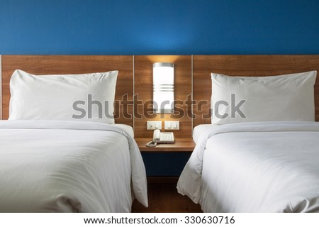 Twin bed with wood headboard. - stock photo