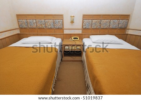 Twin beds neatly done up in a high class hotel room. Suitable for concepts such as travel, tourism, vacation and holiday. - stock photo