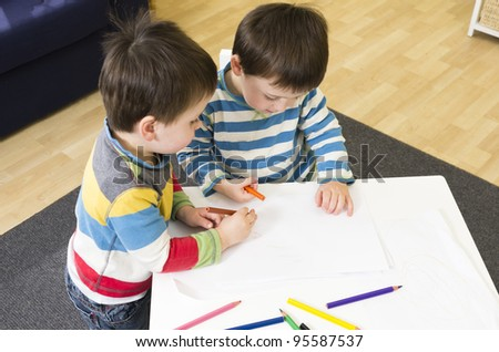 Twin boys drawing at a table together - stock photo