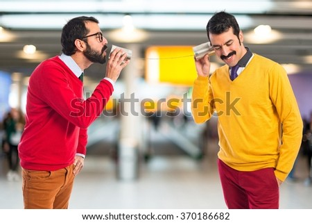 Twin brothers talking through a tin phone  - stock photo