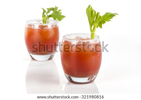 Twin Clamato cocktail glasses. Selective focus over two round glasses of Clamato drinks.  - stock photo