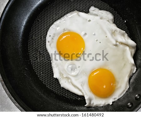 twin fried eggs on the pan - stock photo
