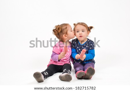Twin girls eating ice cream and kissing - stock photo
