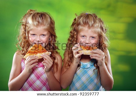 Twin girls eating pizza on the green background - stock photo