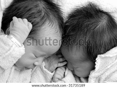 Twin girls sleeping together - stock photo