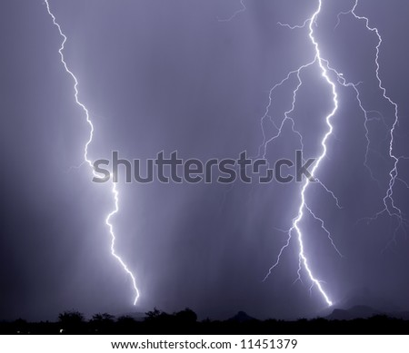 Twin lightning bolts strike a mountain foothill and a stand of saguaro cacti - stock photo