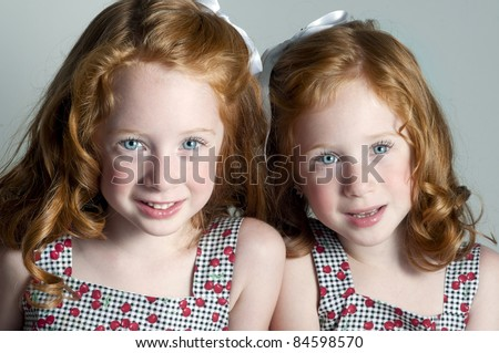 Twin little girls with red hair and blue eyes - stock photo