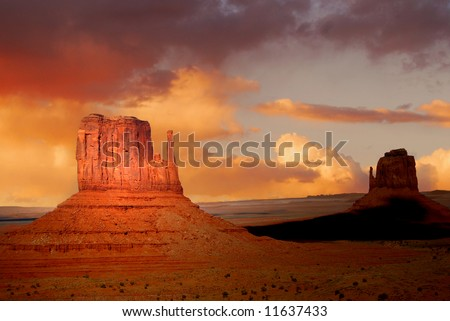 Twin peaks of rock formations in the Navajo Park of Monument Valley Utah known as The Mittens - stock photo