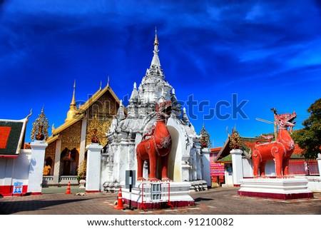 Twin Singa in front of the door Wat PHRATHAT HARIPHUNCHAI in Thailand - stock photo