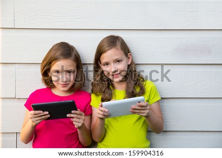 Twin sister girls playing with tablet pc happy on white wall looking camera - stock photo