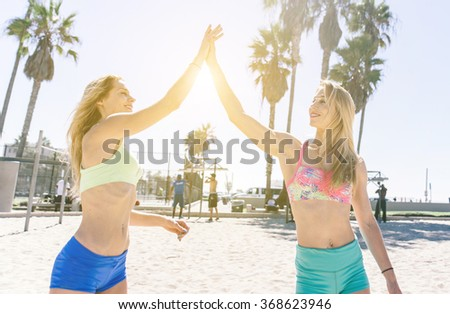 Twin sister making sport training together. Fitness girls giving high five to each others. concept about sport and fitness - stock photo
