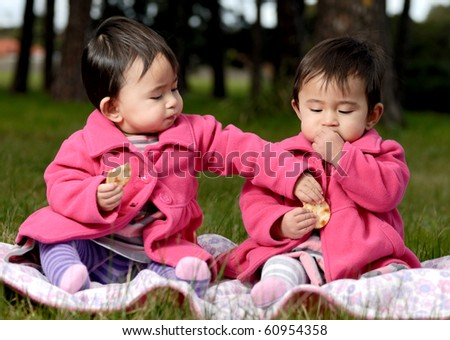 Twin sisters eating snack - stock photo