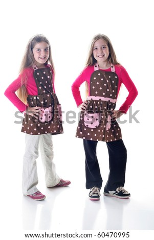 twin sisters in polka dot aprons on white - stock photo
