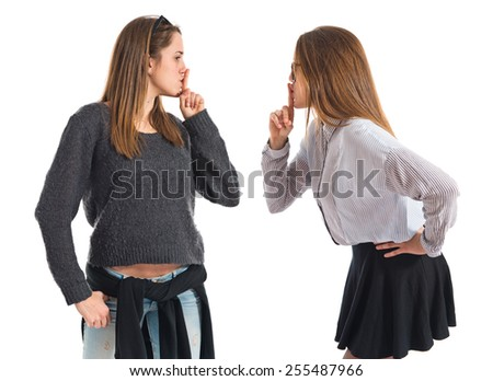 Twin sisters making silence gesture