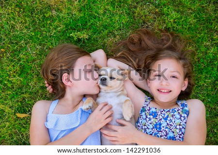 twin sisters playing with chihuahua dog lying on backyard lawn - stock photo