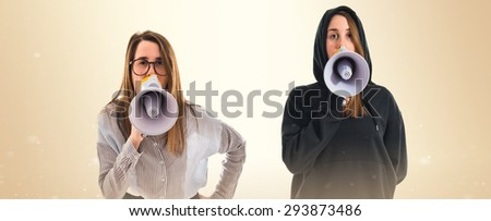 Twin sisters shouting by megaphone over ocher background