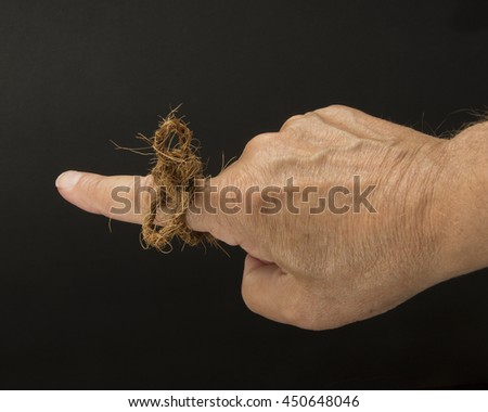 Twine used as a memory trigger/Reminder Technique/Finger with a string - stock photo
