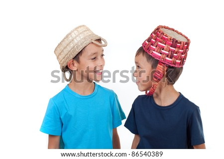 twins playing with wicker baskets on their heads isolated on white - stock photo