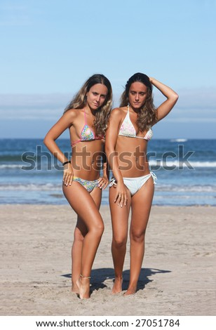 twins posing in the beach - stock photo