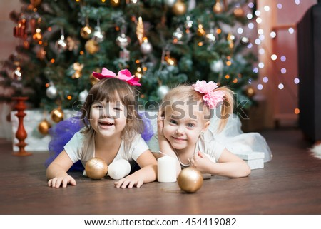 twins skirts tutu near a new year  / Christmas tree grimace lying on his stomach - stock photo