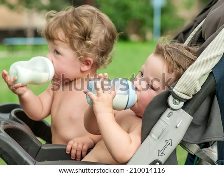 twins suck a bottle with milk - stock photo