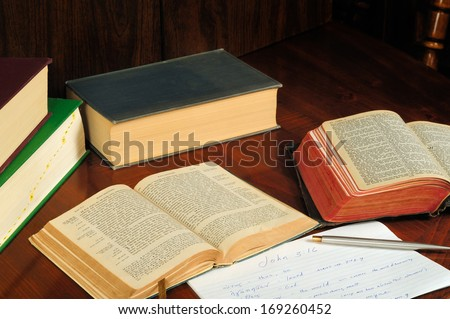 TWINSBURG, OH - JANUARY 16, 2011: Photo of two open Bibles, one in Greek, with other books and study notes, illustrating the concept of researching the original language in Christian Bible study. - stock photo