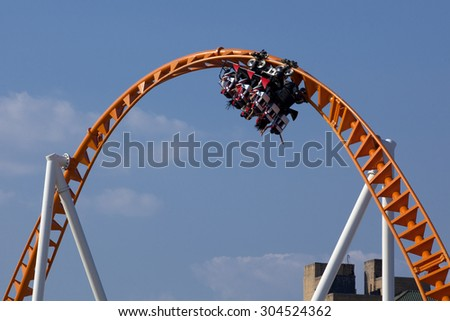 Twist and turns of a modern steel roller coaster. - stock photo