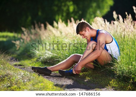 Twisted ankle. Young runner touching his sprained leg