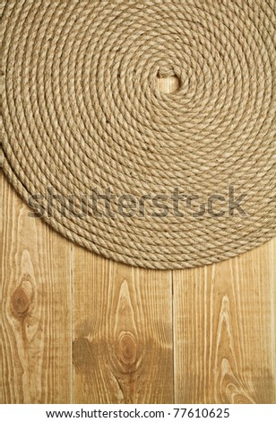 Twisted rope on wooden background - stock photo