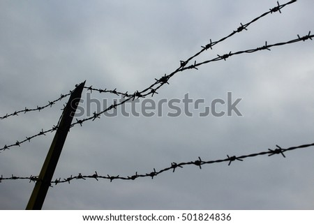 Twisted Wire Fence Sillouhette With Cloudy Sky Background