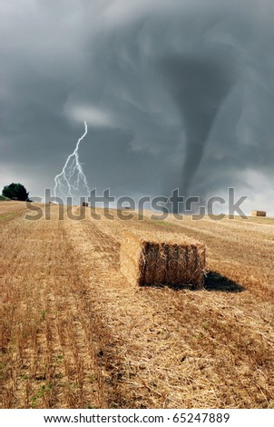 twister lightning and bales of hay in the morning - stock photo