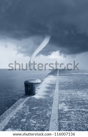 twister on the sea under dramatic sky - stock photo