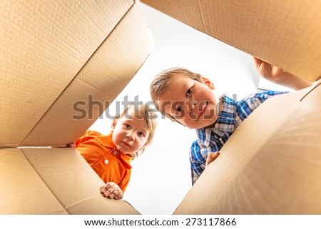 Two a little boys opening cardboard box and looking inside with surprise.