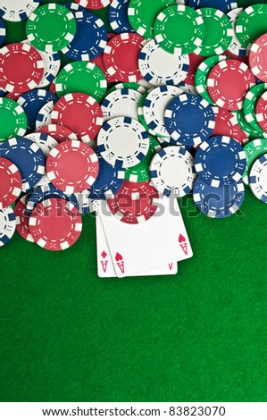 two aces and poker chips on a green felt - stock photo
