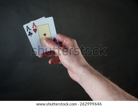 two aces in hand on gray background