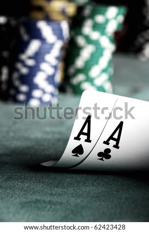 two aces on green table with blurry chips and background - stock photo
